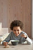 Boy happy eating a bowl of soup