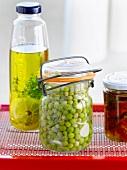 Ein Glas eingemachte Erbsen und Thymian-Zitronen-Öl im Hintergrund