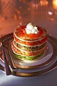 Blini mille-feuille garnished with salmon, avocado, quinoa and fish roe