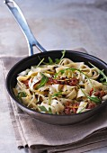 Pan-fried pasta with bacon and rocket lettuce