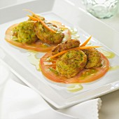 Zucchini croquettes on thinly sliced tomatoes