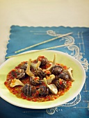 Snails with artichokes, tomato sauce with Vermouth and thinly chopped vegetables