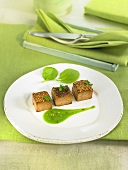 Tofu cubes coated with linseeds, pureed spinach sauce