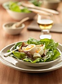 Spinach salad with soft-boiled egg, anchovies and roquefort on bread