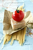 Spaghettis, parmesan and a tomato on a road map of Italy