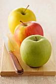 Drei Apfelsorten auf Holzschneidebrett