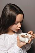 Junges Mädchen bläst in eine Tasse heiße Schokolade