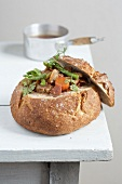 Stewed vegetables served in a round loaf of bread
