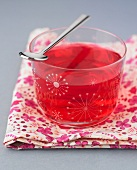 Rote Götterspeise in Glas mit Teelöffel