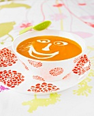 Kürbissuppe mit lustigem Gesicht aus Sahne