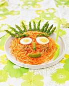 Lustiges Gesicht aus geraspelten Karotten und Spargel