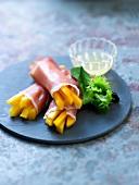 Mango sticks wrapped in raw ham