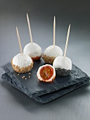 Cherry tomato and cheese balls coated with sesame seeds or poppy seeds
