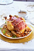 Roast capon coated with ham and stuffed with white sausage,röstis
