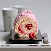 Pink biscuit and raspberry rolled log cake