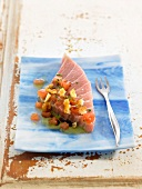 Raw piece of tuna with tomatoes and small croutons