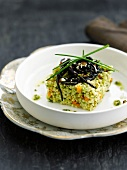 Millet with herbs and hazelnuts topped with squid ink spaghetti