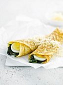 Rolled pancakes garnished with spinach and hard-boiled eggs