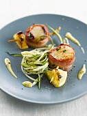 Scallops wrapped in bacon and sliced zucchinis