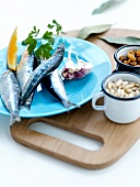 Ingredients for stuffed sardines with pine nuts,raisins,bay leaves and orange sauce