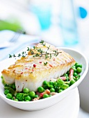 Piece of cod with thyme and pink peppercorns,peas with diced bacon