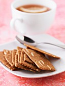 Cinnamon and thinly sliced almond cookies, a cup of coffee