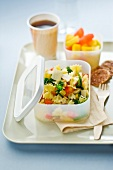 Lunch tray :pasta salad,fruit salad,paper cup of tea and cookies