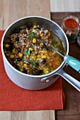 Preparing a broth with rice, sweetcorn, red kidney beans and Espelette pepper