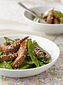 Thinly sliced duck breast with honey and sesame seeds,sugar peas