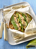 Sliced chicken breasts with zucchinis,sweet peas and spelt cooked in wax paper