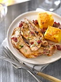 Sliced duck breast with cranberries and grilled polenta