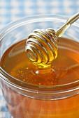 Honey spoon on a pot of honey