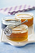 Pots of honey and honey spoon