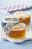 Pots of honey and honey spoon