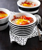 Small casserole dishes of coodled egg with red peppers and pata negra ham