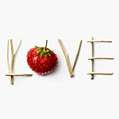 Love written with strawberry and branches