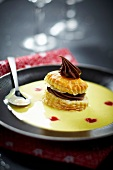 Flaky pastry with chocolate garnish and custard