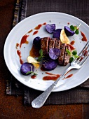 Thick bison steak with purple potatoes,berry sauce