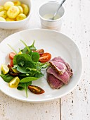 Sliced beef fillet with tomato and baby spinach salad