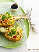Thailändischer Shrimp-Reissalat mit frischem Koriander in Ananashälften serviert