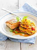 Thick piece of grilled salmon,tagliatelles in tomato sauce with thin strips of zucchinis