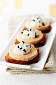 Foie gras on slice gingerbread and topped with pear foam and balsamic vinaigar pearls