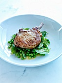 Grilled pork chop with minty peas