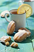 Madeleines with frosting and a cup of lemon tea