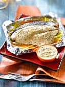 Sea bream and winter vegetables cooked in aluminium foil, creamy white wine sauce