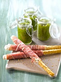 Raw ham sesame bread sticks and Pesto