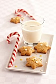 Star-shaped Christmas cookies with a glass of milk and barley sugar