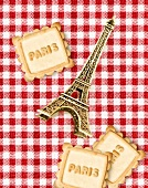"""Composition with a mini Eiffel Tower and cookies with the inscription""""Paris"""" on a red and white checkered tablecloth"""