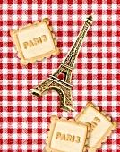 Komposition mit Mini-Eiffelturm und Plätzchen mit Aufschrift Paris auf rot-weiss-karierter Tischdecke
