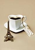 Komposition mit Mini-Eiffelturm und herzförmiger Tasse Kaffee